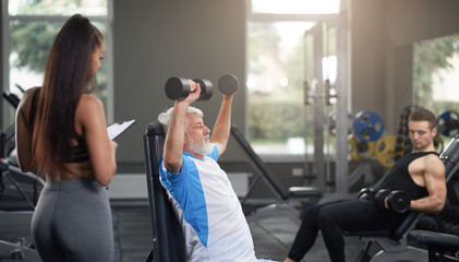 Female personal trainer observing clients doing exercises.