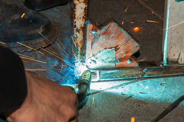 An experienced person performs work with a welding machine, fixing metal parts, removing blue smoke and yellow sparks and lightning in the industrial production workshop.