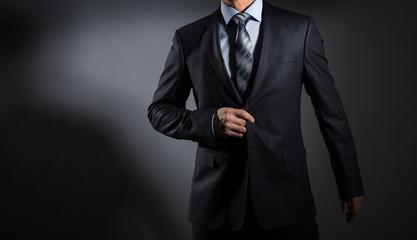 A man in an elegant suit on a dark background. Men's fashion.
