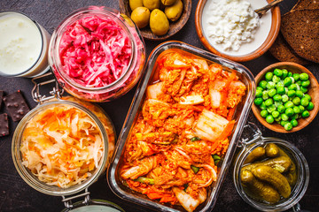 Probiotics food concept. Kimchi, beet sauerkraut, sauerkraut, cottage cheese, peas, olives, bread, chocolate, kefir and pickled cucumbers.