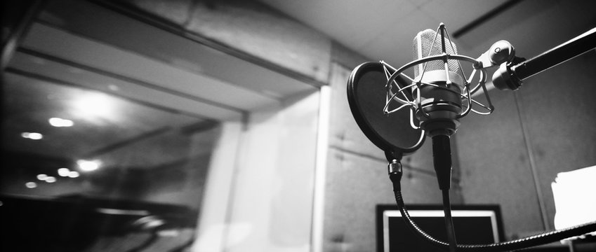 Studio microphone or mic for recording for vocal singer or commercial announcer with shock mount and pop filter on professional tripod in acoustic foam room for best sound and mix process