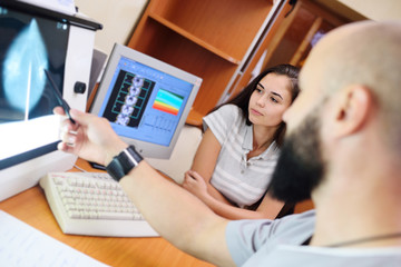 the doctor and the patient are watching a mammogram-the result of x-ray examination of the mammary glands for the prevention of breast cancer