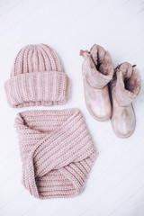 A beautiful knitted hat with a pink scarf and winter boots with natural fur on a white wooden background.