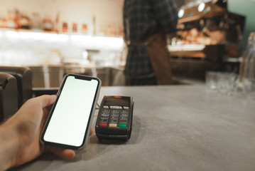 Mobile payment in cafe with smartphone nfc near field communication wireless technology. Paying with smartphone at the coffee shop, while male barista is preparing coffee at the coffee machine.