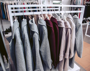 A collection of autumn women's coats hanging on a hanger in a clothing store.