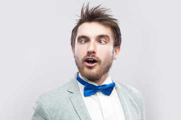 Closeup portrait of crazy funny handsome bearded man in casual grey suit and blue bow tie standing with crossed eyes and looking. indoor studio shot, isolated on light grey background.