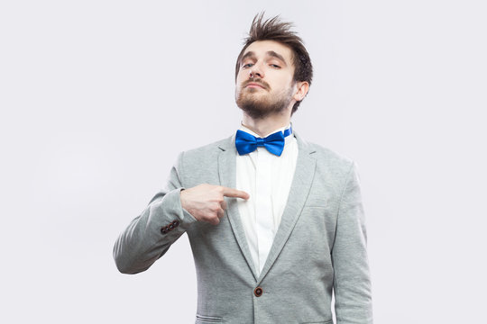 Portrait of proud satisfied haughty handsome bearded man in casual grey suit and blue bow tie standing, pointing himself and looking at camera. indoor studio shot, isolated on light grey background.