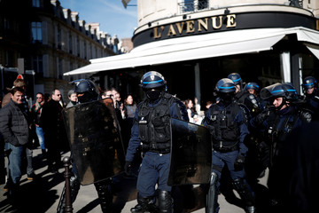 """Riot police officers guard a restaurant during a demonstration by the """"yellow vests"""" movement in Paris"""