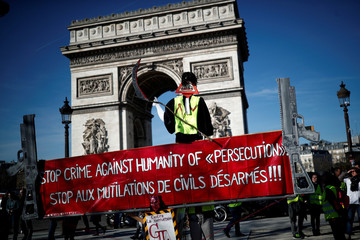 """Protesters wearing yellow vests gather at the Arc de Triomphe during a demonstration by the """"yellow vests"""" movement in Paris"""