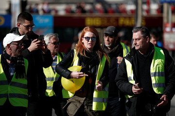 """French activist Ingrid Levavasseur speaks with protesters wearing yellow vests during a demonstration by the """"yellow vests"""" movement in Paris"""
