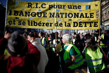 """Protesters wearing yellow vests walk down the Champs-Elysees avenue during a demonstration by the """"yellow vests"""" movement in Paris"""