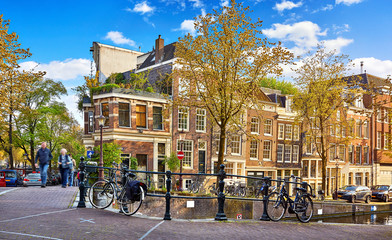 Fototapete - Street of Amsterdam city. Netherlands. Bridge over channel with traditional dutch houses and bicycles. Evening time warm sunlight, blue sky with clouds. Spring cityscape, green and yellow autumn.