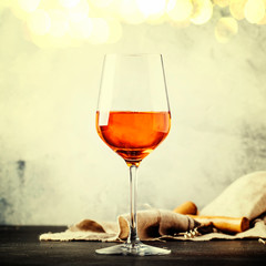 Trendy food and drink, orange wine in glass, gray table background, space for text, selective focus. Square image, vintage toning