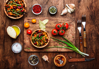 Green beans with roots, vegetables, mushrooms, spices and tomatoes, vegan bowls. Food cooking background, vintage wooden rustic table. View from above