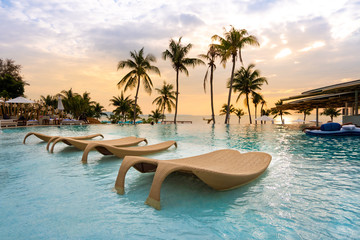 luxury swimming pool on sea view and chair in hotel resort with sunrise time