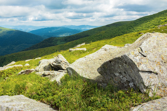 massive rocks on a grassy meadow. beautiful summer landscape in mountains. sunny weather