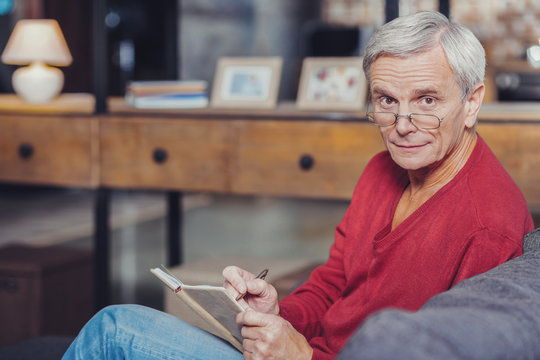 Worried pensioner making notes in his notebook and looking impressed