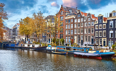Fototapete - Amsterdam, Netherlands. Floating Houses, houseboats and boats at channels by banks. Traditional dutch dancing houses among trees. Evening autumn street above water blue sky with clouds.