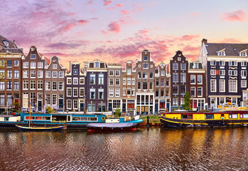 Fototapete - Amsterdam, Netherlands. Floating Houses and houseboats and boats at channels by banks. Traditional dutch dancing houses among trees. Evening autumn street above water pink sunset sky with clouds.