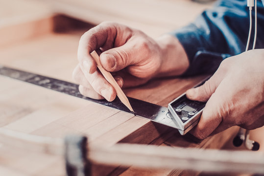 Carpenter in the workshop marks out the details of the furniture cabinet using a setsquare