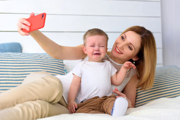 Mother with cry child baby boy photoshooting on red smartphone selfie in home room
