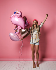 A beautiful young joyful girl is holding a bunch of pink balloons on a pink pastel background.