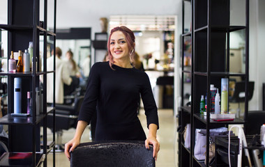 Beautiful young hairdresser in beauty salon Wall mural