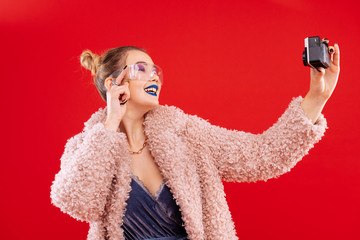 Woman wearing pink fluffy coat smiling while making selfie