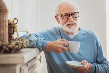 Smart elderly man drinking coffee while having break