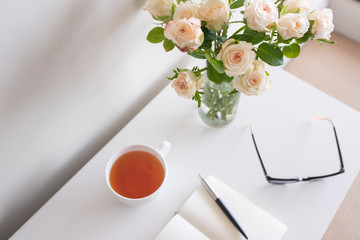 High angle view of pale pink roses in glass with home office desk in background including cup of team, notebook, pen and glasses (selective focus)