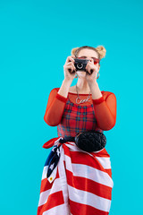 Blonde woman wearing red bodysuit making photo with American flag