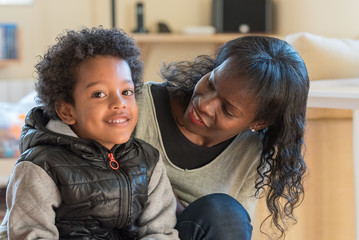 mother and son posing happily before the camera in the living room of home. Afro-single family afro