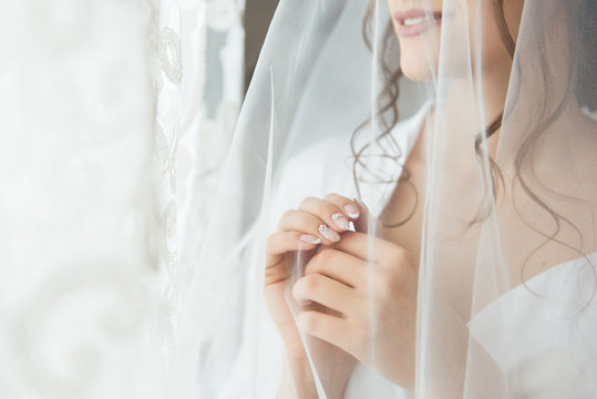 Bride in a wedding dress and veil looking at the window, waiting for the groom at the morning