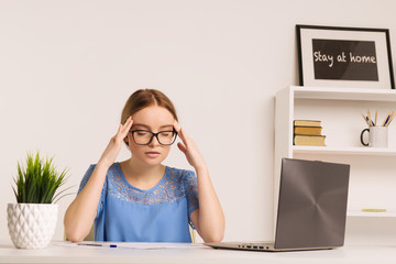 Portrait of tired businesswoman having headache at workplace after working with computer