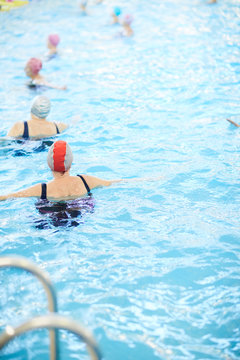 Back view portrait of senior women exercising in swimming pool, copy space