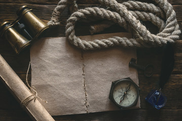 Blank traveler notebook, compass, binoculars, mooring rope and inkpot with a quill pen on a wooden table background mockup. Adventurer notes.