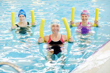 Group of active senior women exercising in swimming pool, holding pool noodles and smiling at camera, copy space
