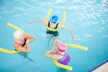 Top view at group of active senior women working out in swimming pool holding pool noodles, copy space