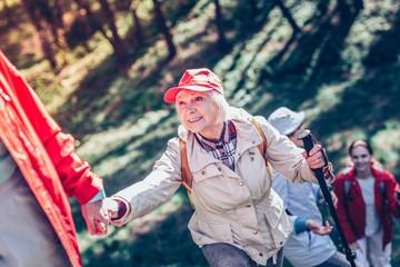 Beaming elderly lady wearing comfortable clothing hiking
