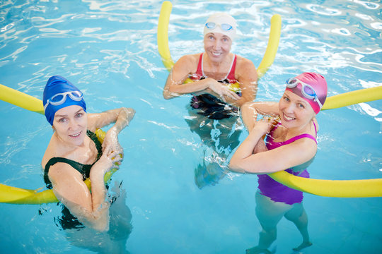 Above view at group of active senior women swimming in pool and smiling at camera