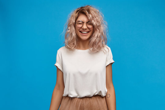 Emotional charming young European female in trendy glasses laughing, closing eyes and smiling broadly, showing her white perfect teeth. Attractive girl in good mood having fun, posing at blue wall