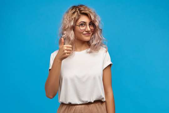 Picture of good looking friendly young Caucasian female wearing stylish clothes and round eyeglasses making approval gesture, showing thumbs up sign at camera and smiling happily, posing at blue wall