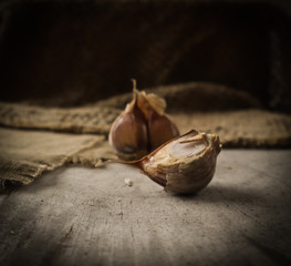 Garlic cloves and natural linen napkin on rustic wooden background