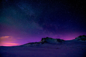 Starry sky behind mountains just before sunrise