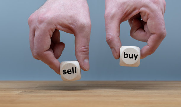 """Hands are holding two cubes with the words """"sell"""" and """"buy"""". One hand rises the cube with the word """"buy""""."""