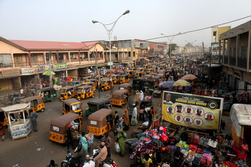 Taxis called in a local language Keke-Napep move in a street after the postponement of the presidential election in Kano