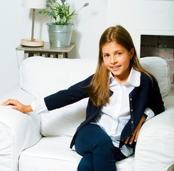 little cute brunette girl at home interior happy smiling close up in chair, lifestyle people concept