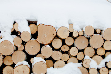 Firewood stacked in winter. Wood pile with snow stacked for firewood. Chopped stock of firewood under snow. Piles of snow covered firewood at cold winter day