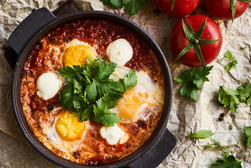 Shakshuka with eggs, tomatoes and parsley in a frying pan, close-up