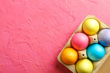 Decorative eggs in cardboard box on color background, space for text. Top view